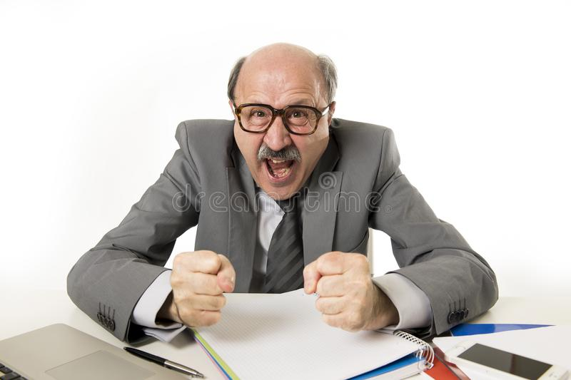 60s bald senior office boss man furious and angry gesturing upset and mad sitting on desk with paperwork in business and job prob royalty free stock photography