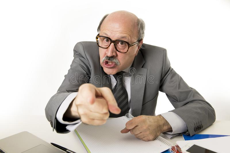 60s bald senior office boss man furious and angry gesturing upset and mad sitting on desk with paperwork in business and job prob royalty free stock image