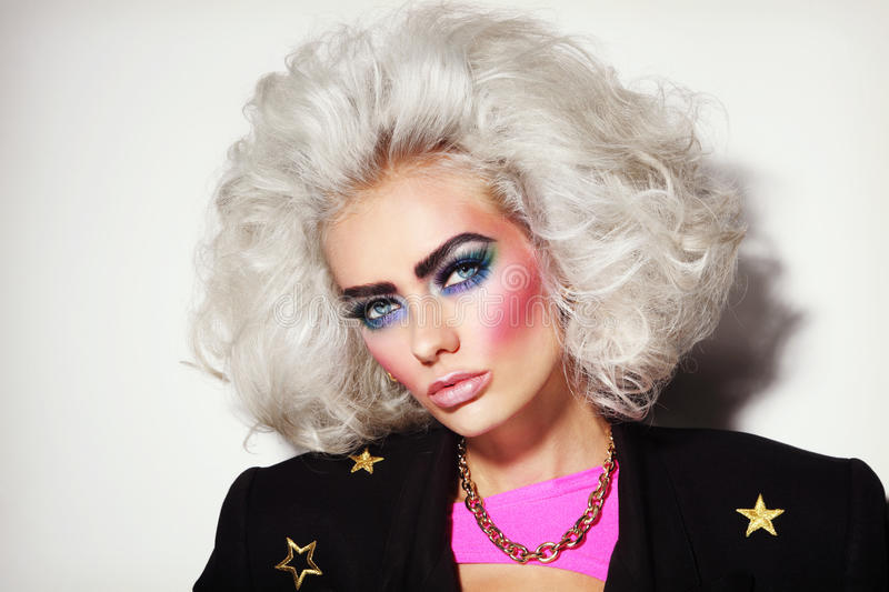 80s beauty. Portrait of young beautiful platinum blond woman with bold eyebrows and 80s style makeup stock images