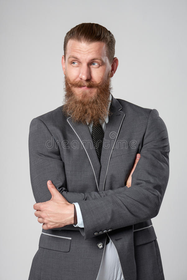 He`s a bit skeptical. A young trendy business man looking to the side with distrust squinting his eyes royalty free stock photography