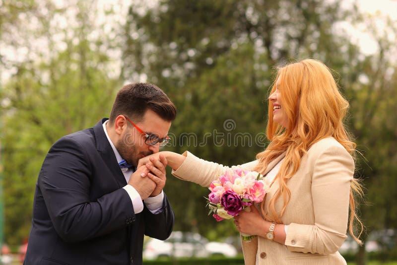 `S Braut des Bräutigams küssende Hand stockfoto