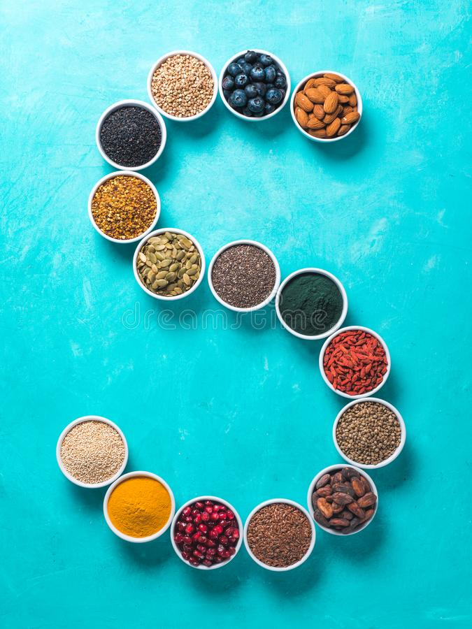 S brief van superfoods in kom op blauwe achtergrond royalty-vrije stock fotografie