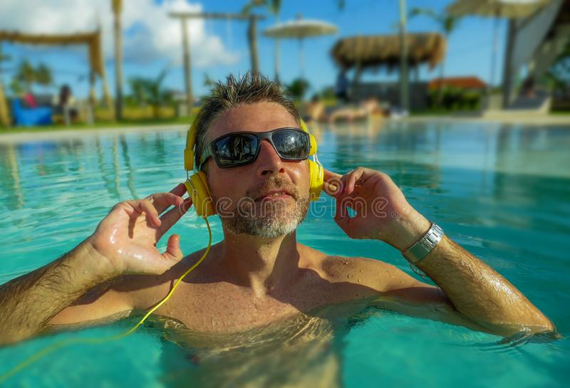 30s cool and relaxed man enjoying playful at tropical luxury resort swimming pool listening to music with headphones feeling. Indulged and fresh having fun in stock photography
