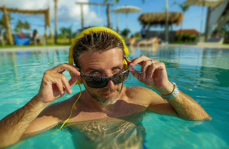 30s cool and relaxed man enjoying playful at tropical luxury resort swimming pool listening to music with headphones feeling. Indulged and fresh having fun in royalty free stock photo