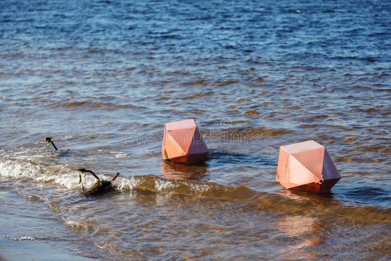 S?curit? sur l'eau Deux grandes balises oranges et un mensonge d'ancre horizontalement au rivage sur l'eau de la baie de rivière photographie stock libre de droits