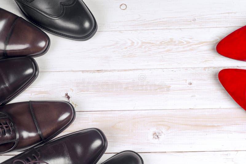 ` S d'hommes et chaussures des femmes rouges de talon haut sur le fond blanc image libre de droits