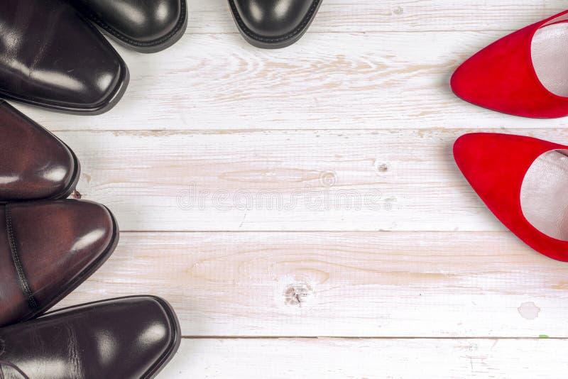 ` S d'hommes et chaussures des femmes rouges de talon haut sur le fond blanc photographie stock