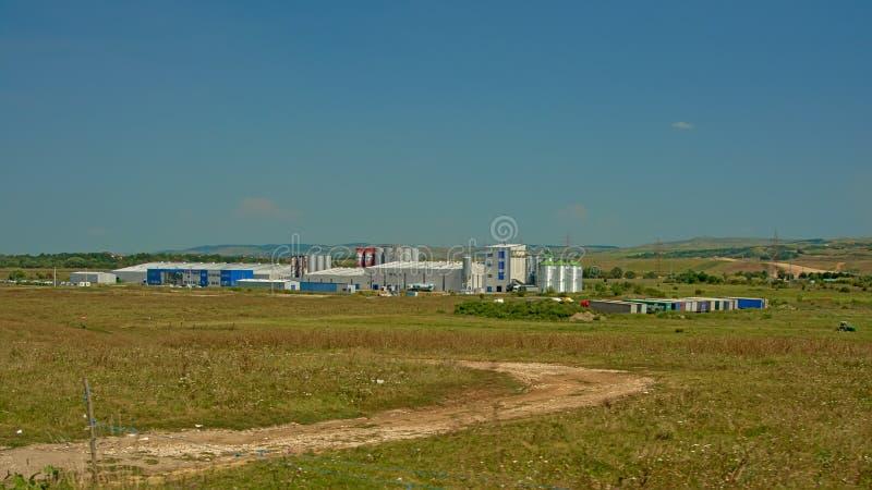 ` S de bâtiment industriel et de silo dans la campagne roumaine photos stock