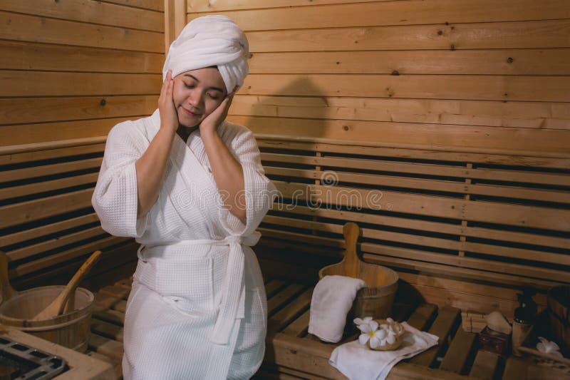 ` S de fille dans la salle de sauna, r?g?n?rant dans la pi?ce en bois tropicale Pour maintenir le corps sain images libres de droits