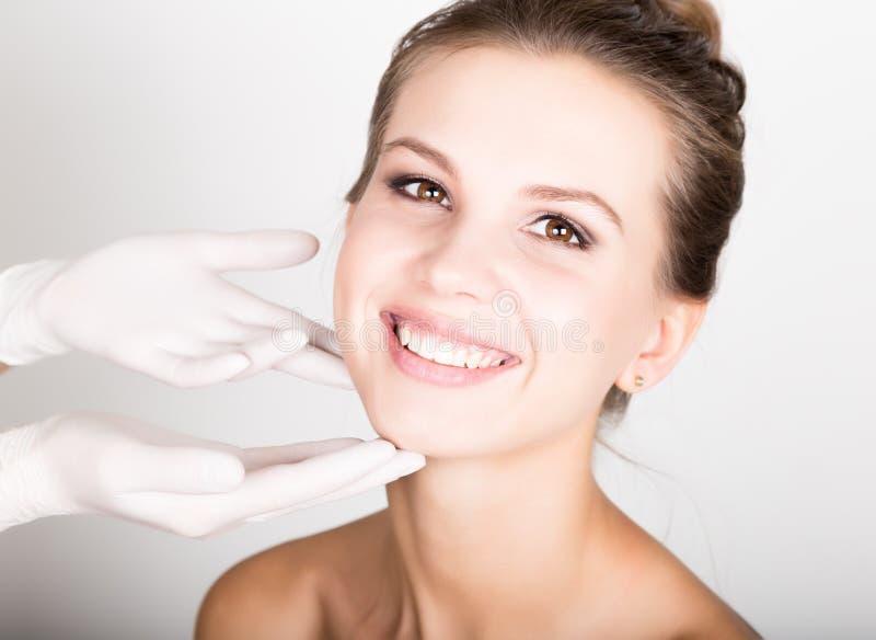 ` S de la mano del cosmetólogo que examina la cara femenina joven hermosa imagen de archivo