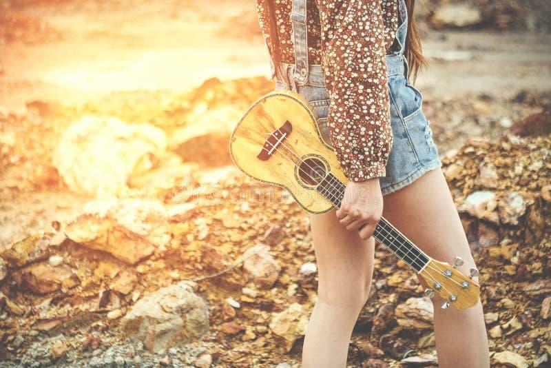 ` S de main de jeune femme tenant l'ukulélé, le grain mou de foyer et le vinta photographie stock libre de droits