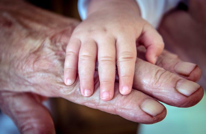 ` S del bebé y vieja mano áspera del ` s de la abuela foto de archivo