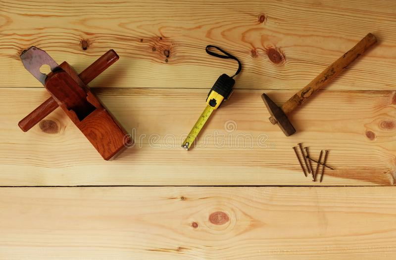 ` S del carpentiere per falegnameria Vecchio aereo del martello e del chiodo e di legno e nastro di misurazione sul fondo di legn immagini stock