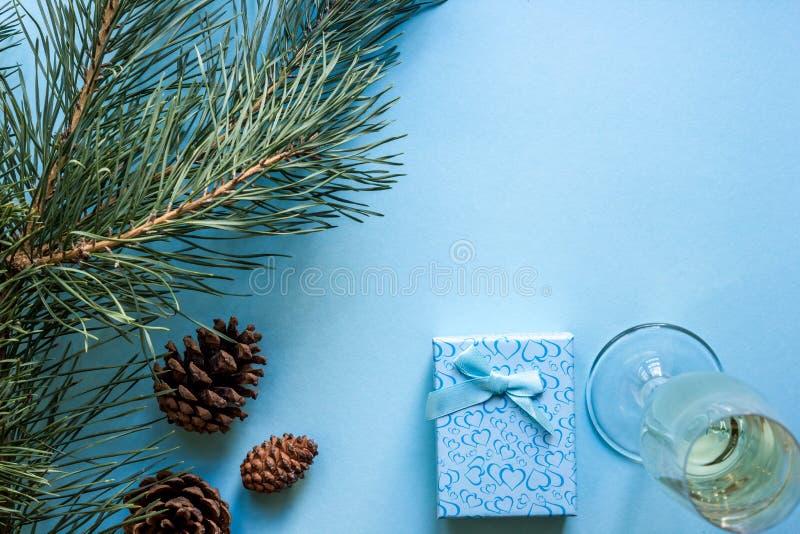 ` S del nuovo anno ancora vita un vetro di champagne, delle decorazioni di Natale e dei rami attillati su fondo blu immagini stock libere da diritti