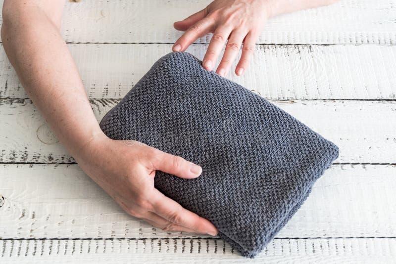 ` S della donna che piega un asciugamano grigio per disporrlo sullo scaffale Stazione termale e benessere, tessuto di Terry del c fotografia stock