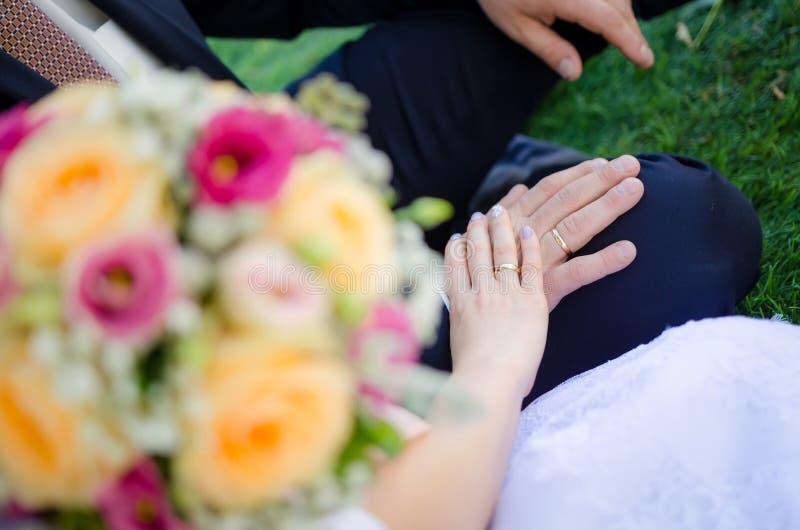` S dello sposo e della sposa che si tiene mano del ` s con le fedi nuziali fotografie stock libere da diritti