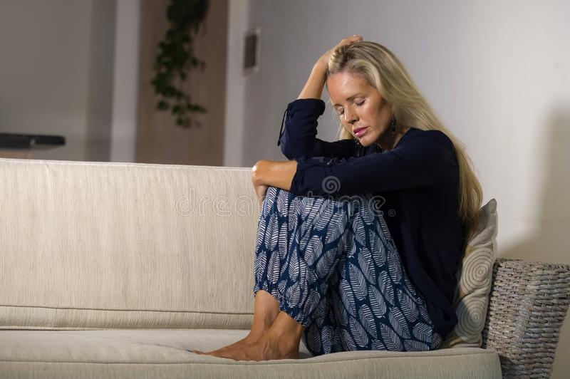 Depressed and anxious beautiful blonde woman suffering depression and anxiety crisis feeling frustrated and thinking lonely at hom royalty free stock photos