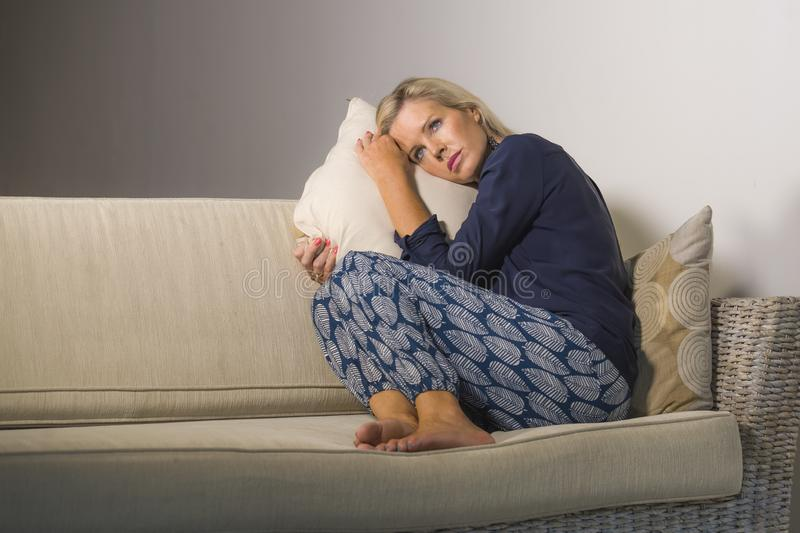 40s depressed and anxious beautiful blonde woman suffering depression feeling frustrated and lonely sitting at home sofa couch tho. Ughtful and pensive in middle royalty free stock image