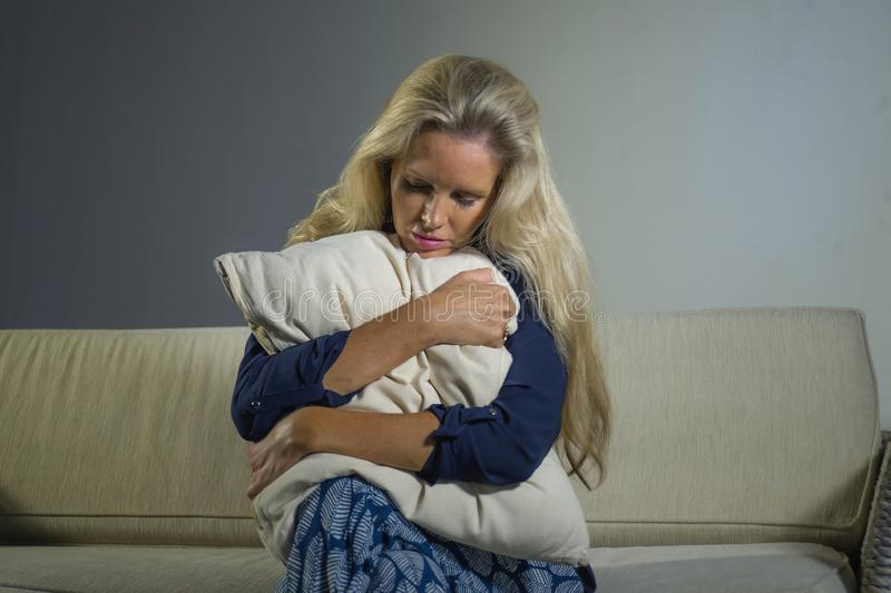 40s depressed and anxious beautiful blonde woman suffering depression and pain feeling frustrated sitting at home sofa couch sad a royalty free stock images