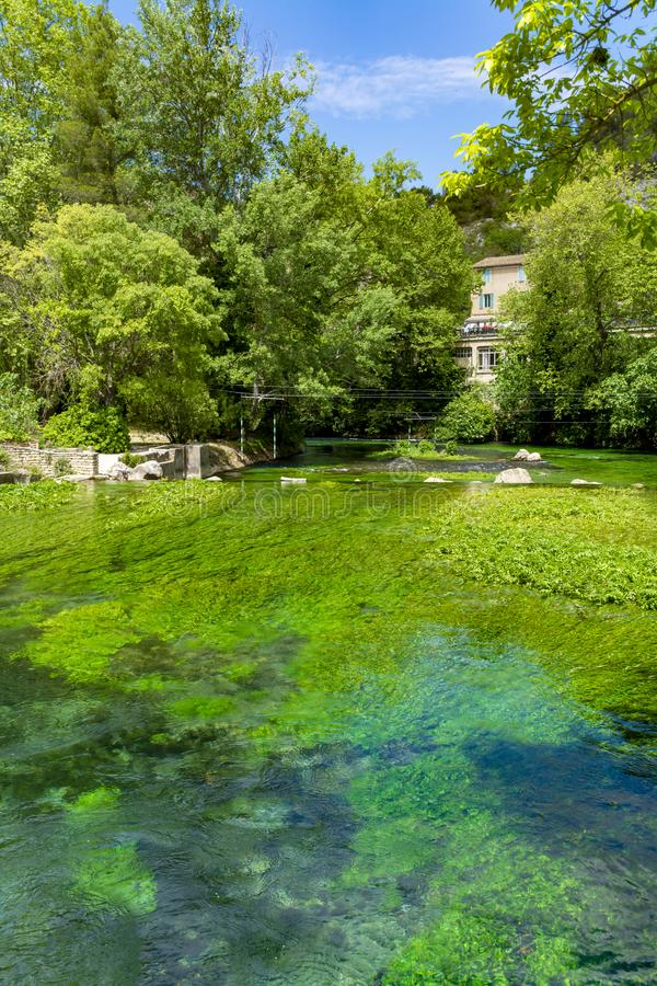 S?der av Frankrike, sikt p? den lilla Provencal staden av poeten Petrarch Fontaine-de-vaucluse med vatten f?r smaragdgr?splan av  fotografering för bildbyråer