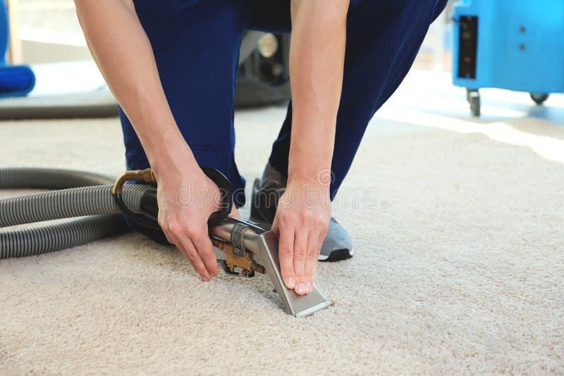 ` S der chemischen Reinigung Angestellter, der Schmutz vom Teppich in der Ebene entfernt lizenzfreie stockfotos