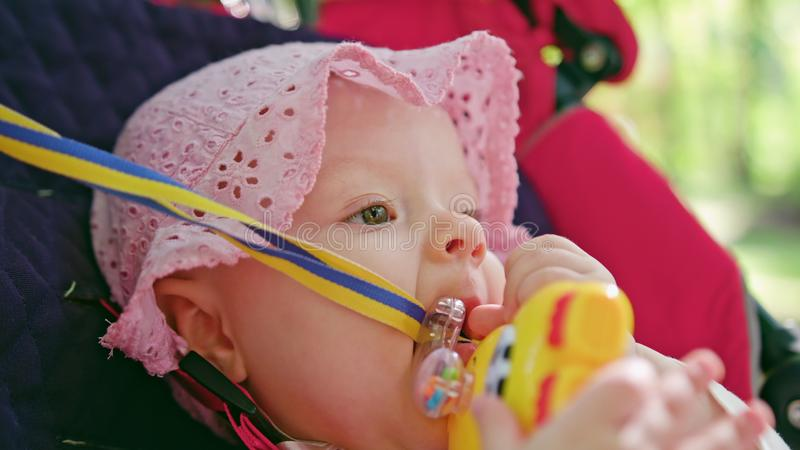 ` S do bebê que senta-se em um carrinho de criança no parque fotos de stock royalty free