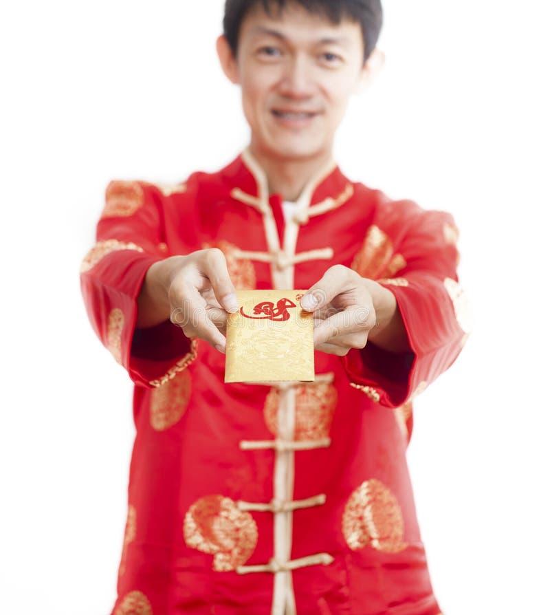S?dostasiatischer Mann in cheongsam H?nden, die rote Pakete, ANG-Kriegsgefangen, lokalisiert auf wei?em Hintergrund halten stockfotografie