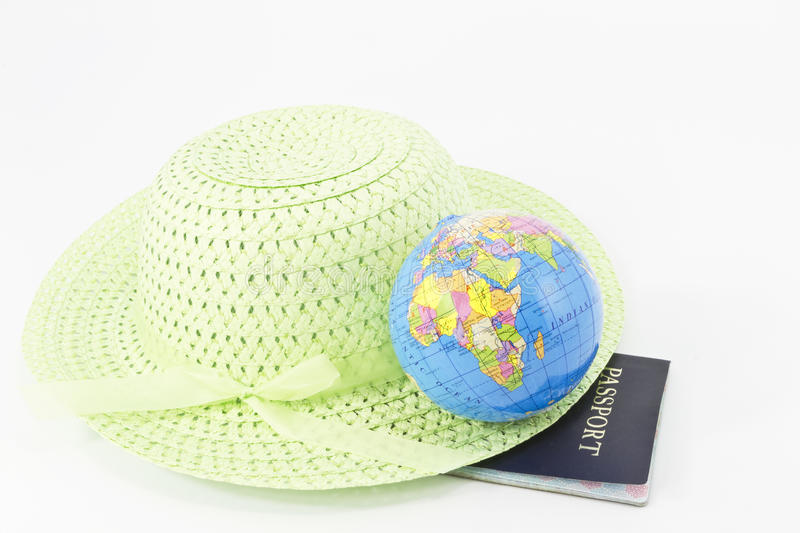 She's Eager to Travel. Wide-brimmed, light green, straw hat is placed with a small glove on its rim and a passport beneath royalty free stock photos