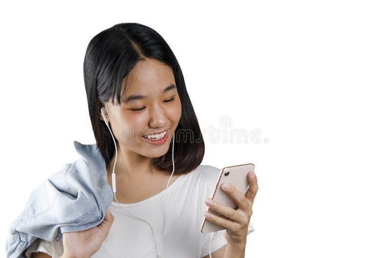 20s eine asiatische junge hörende Frau eine Musik im weißen weißen Hintergrund des Handys lizenzfreies stockfoto