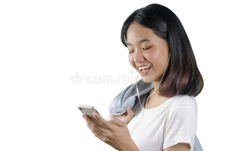 20s eine asiatische junge hörende Frau eine Musik im weißen weißen Hintergrund des Handys stockbild