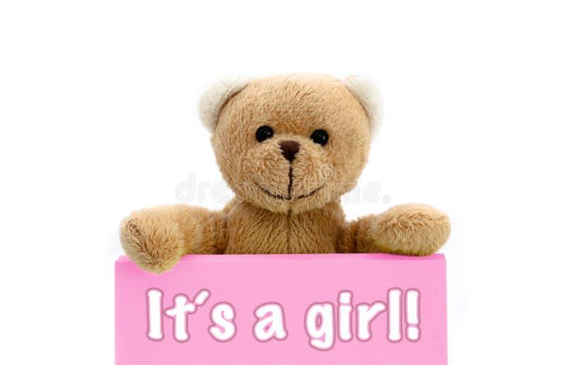 ItÂs eine Mädchenmitteilung geschrieben auf rosa Karte mit dem braunen Teddybären, der mit den zwei Händen die Anmerkung mit der  stockfoto