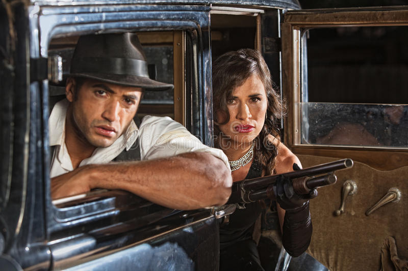 1920s Era Gangster Duo. 1920s gangster duo in car with shotgun on look out stock photography
