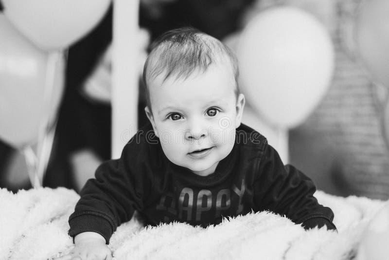 S??es Baby mit den gro?en blauen Augen, die auf Bauch und dem L?cheln liegen stockbild