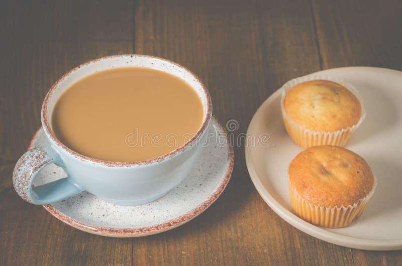S??es H?rnchen und ein Tasse Kaffee im Hintergrund Muffins und Becher mit Cappuccino zum Frühstück stockfotografie