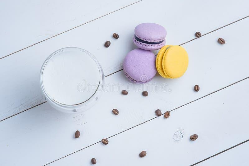 S??es k?stliches Veilchen und gelbe macarons und Schale Latte oder americano und zerstreute Kaffeebohnen auf wei?em h?lzernem lizenzfreies stockbild