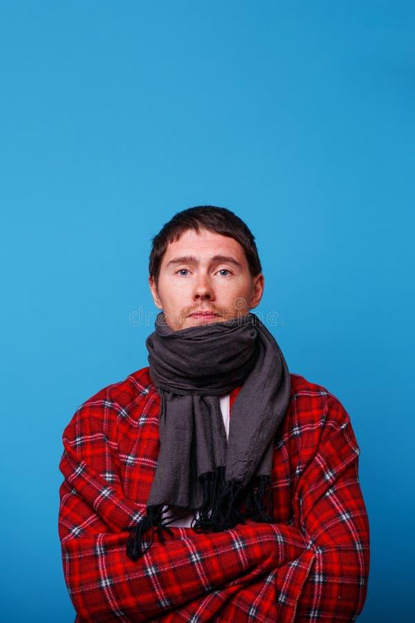 S'est enveloppé chez un homme malade couvrant avec l'écharpe est fond bleu de standingon images libres de droits