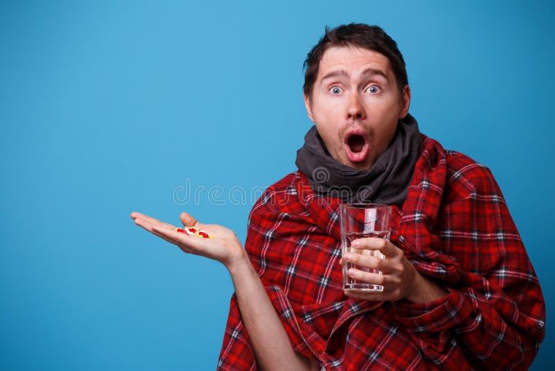 A s'est enveloppé chez un homme malade couvrant avec les comprimés et la tasse dans des ses mains photo stock