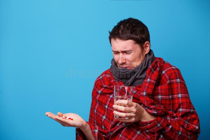 A s'est envelopp? chez un homme malade couvrant avec les comprim?s et la tasse dans des ses mains photos libres de droits