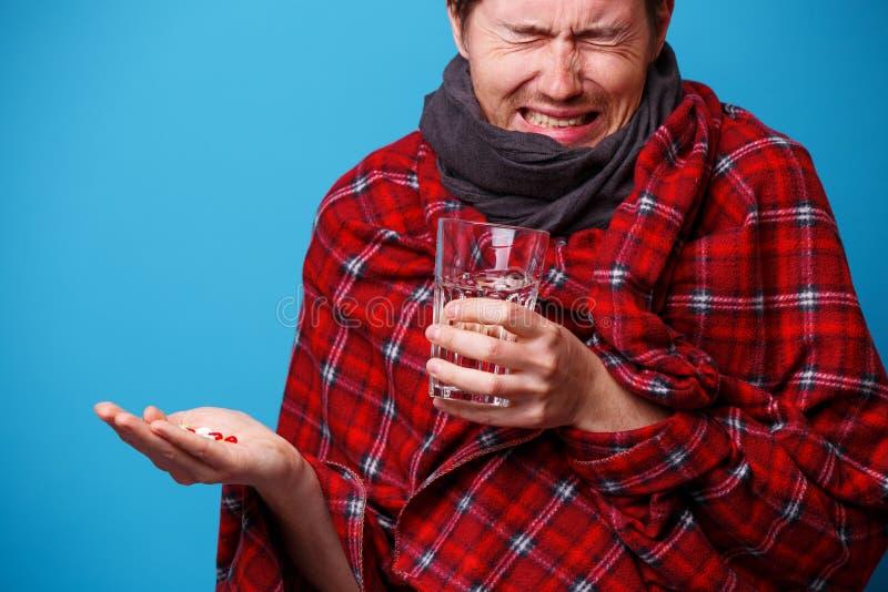 A s'est envelopp? chez un homme malade couvrant avec les comprim?s et la tasse dans des ses mains photographie stock libre de droits