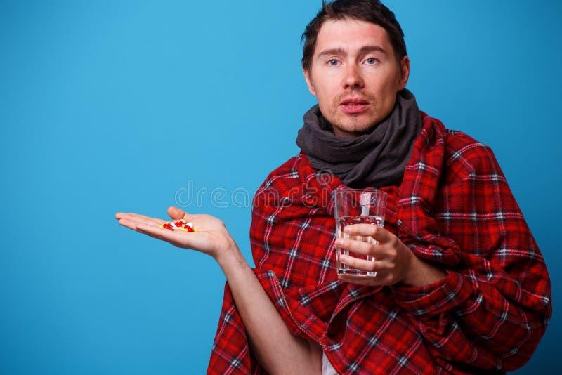 A s'est envelopp? chez un homme malade couvrant avec les comprim?s et la tasse dans des ses mains photos stock