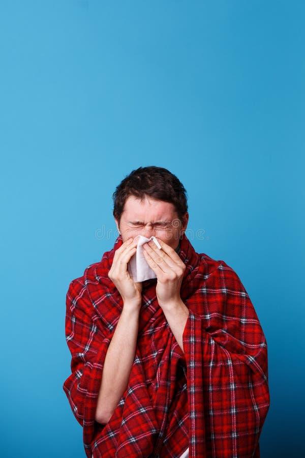 A s'est envelopp? chez un homme malade couvrant souffle son nez dans le mouchoir blanc photographie stock libre de droits