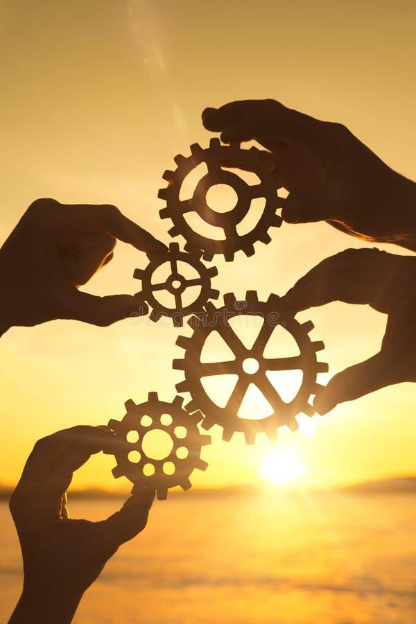 ` S för fyra affärsmän räcker mot efterkrav ett pussel av kugghjul mot solnedgången arkivbilder