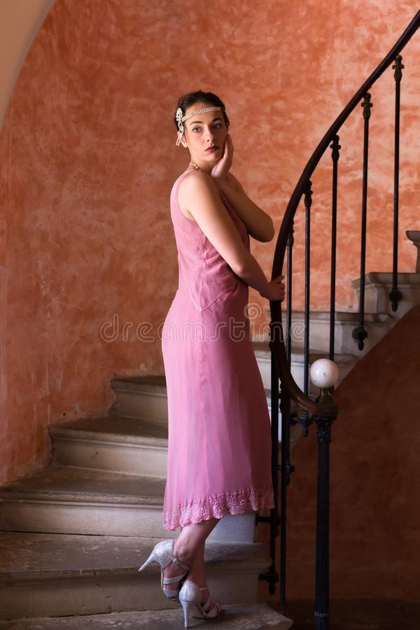 1920s flapper dress woman on stairs. Beautiful woman in authentic retro twenties flapper dress and headband walking down an antique spiral staircase royalty free stock image