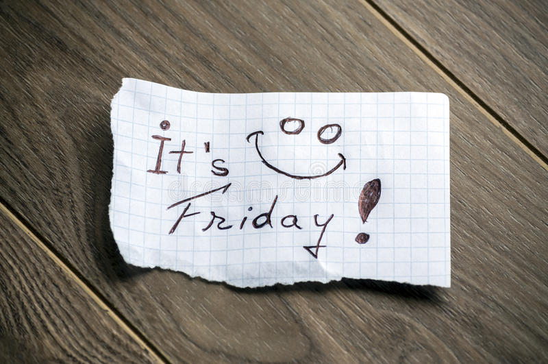 It's Friday. Hand writing text on a piece of paper on wood background royalty free stock photo