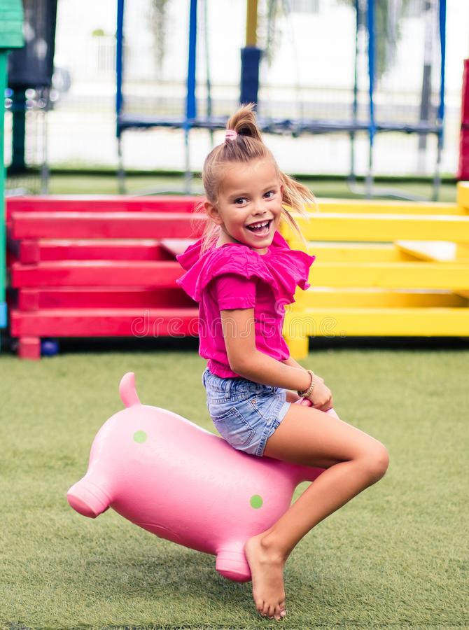 It`s always fun. Little happy girl spending time on playground. Looking at camera. Space for copy. Close up stock photo