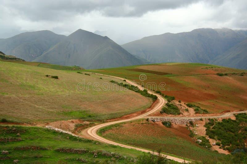 S gebogene Landstraße schnitt tief durch Landwirtschaftsbereich in das Tal von Anden-Bergen, Cusco, Peru lizenzfreies stockfoto