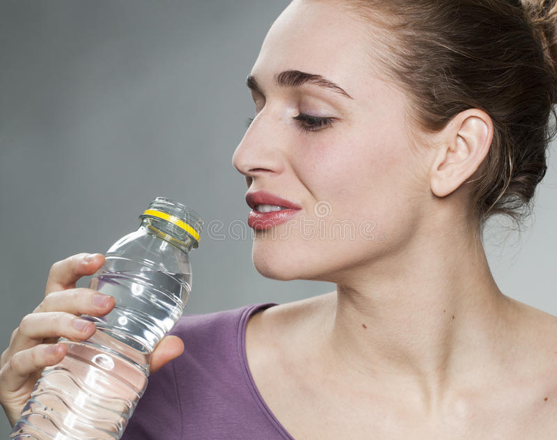 20s girl drinking fresh zesty water in studio. Young beautiful woman wearing purple shirt drinking a bottle of citrus mineral water viewed from profile royalty free stock images