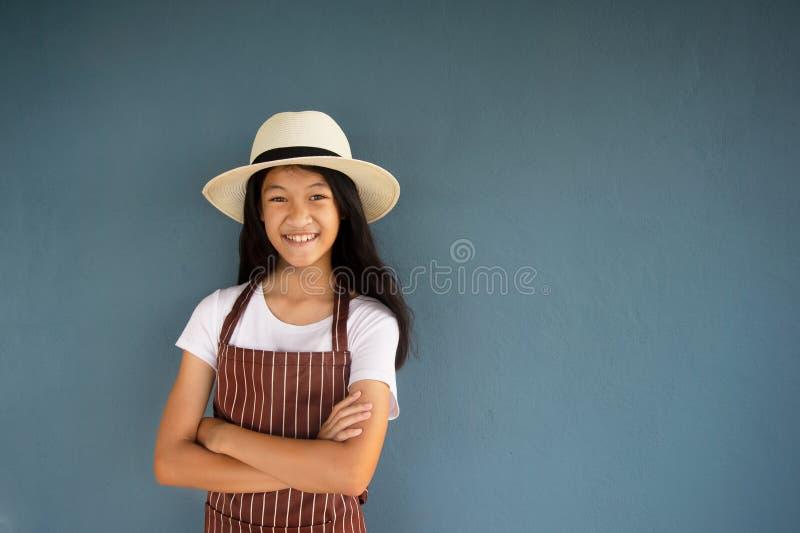 11s glimlachend jong mooi meisjesportret in de zomerhoed en gestreepte bruin globaal met blauwe cementmuur stock fotografie