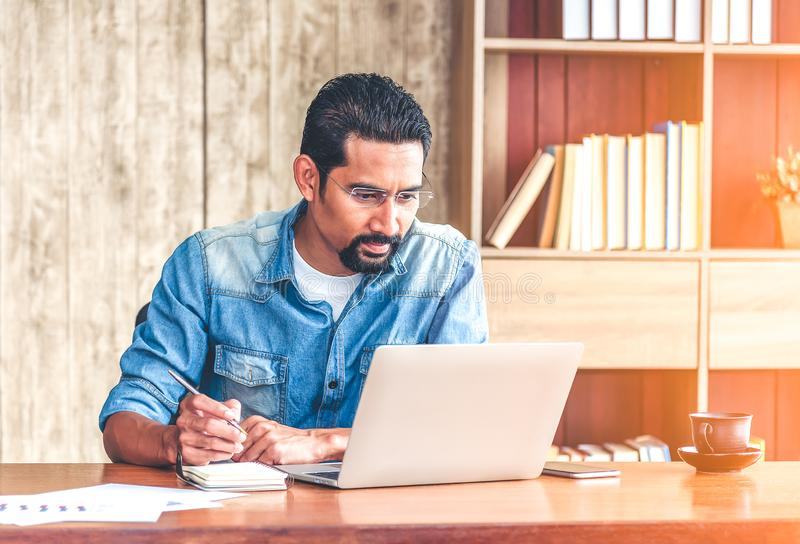 30s handsome businessman take a short note on paper while reading article from internet.  Modern arab businessman in casual royalty free stock image