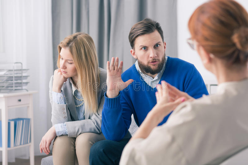 It's her fault, she betrayed me... Man and women during session with marriage counselor stock photo